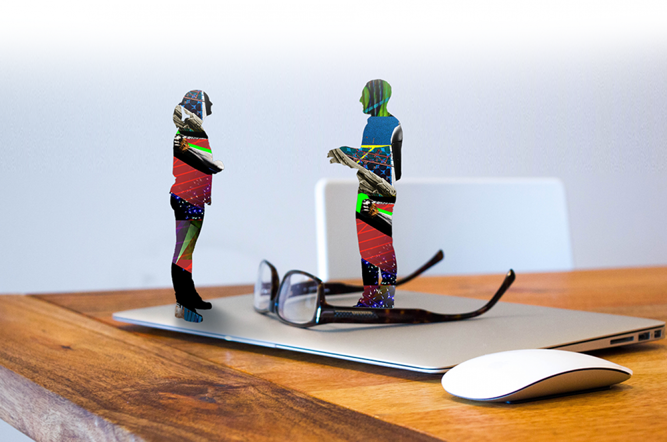 two graphic style people chatting on top of laptop on desk with glasses and mouse